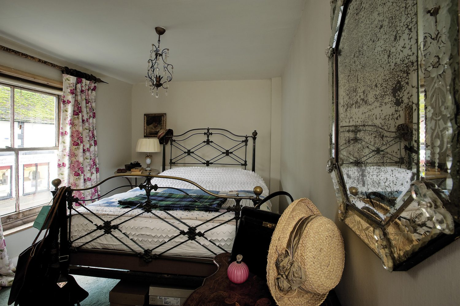 """On closer inspection, the iron bedstead in the master bedroom, with its delicate lattice pattern, is not the usual Victorian black but is actually painted verdigris green with a garnet red Greek key pattern traced around the posts. """"Most iron beds have been smothered in black paint,"""" explains Brad, """"but originally, iron beds were painted in a variety of colours and featured little patterns or designs."""""""