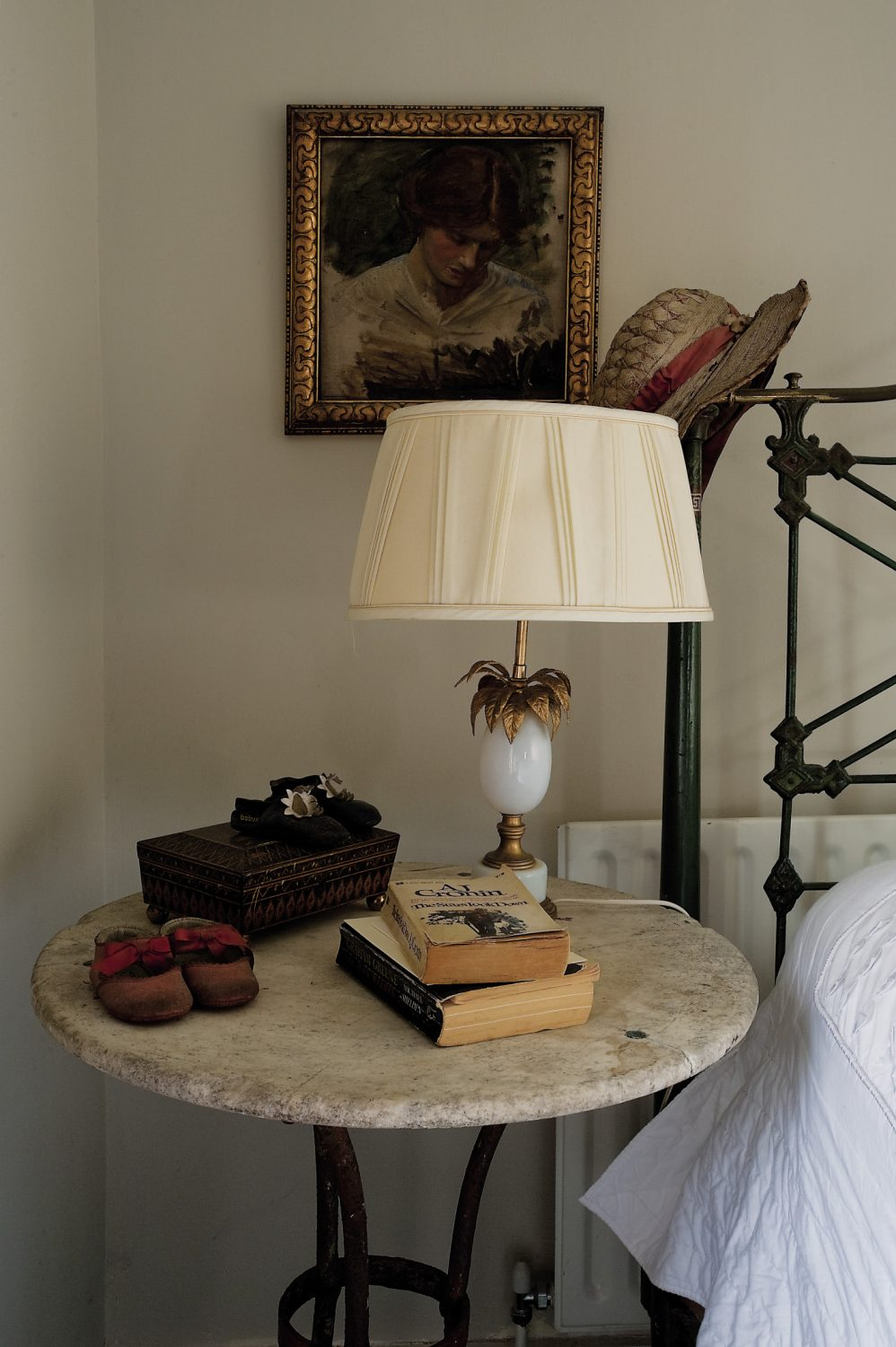 A small circular metal table stands to one side of the bed and an opaline glass lamp with gold palm leaves sprouting from the top adds a dash of French glamour...