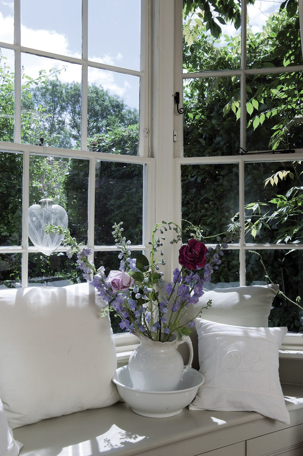 The dining room is painted in pale, Dior grey and white, and is bathed in warm sunlight from the south-facing bay window. A circular table has been dressed with a vintage damask cloth and set for breakfast