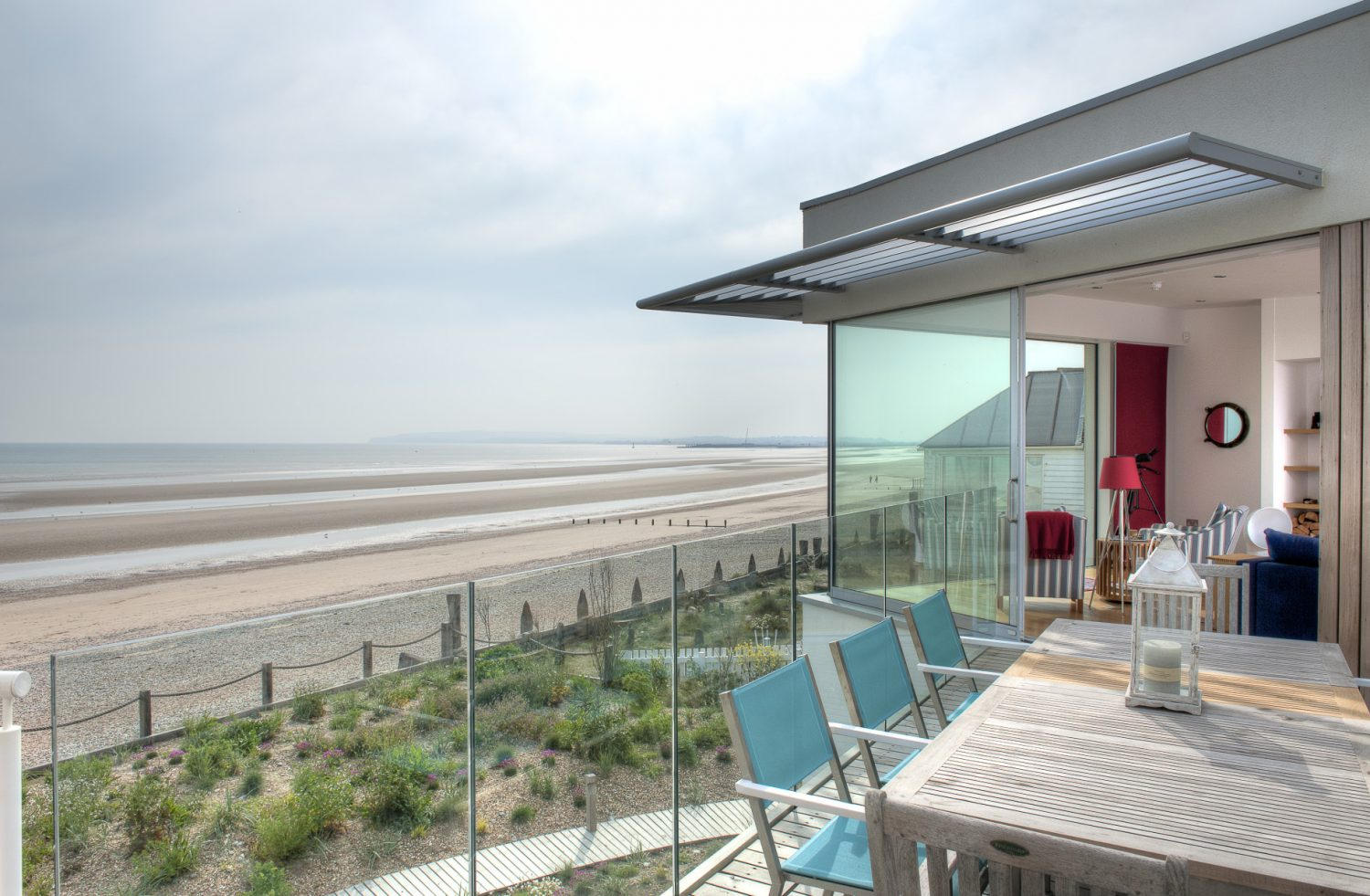 On the first floor at the front of the building, two walls are of floor to ceiling glass allowing an uncompromised view out to sea