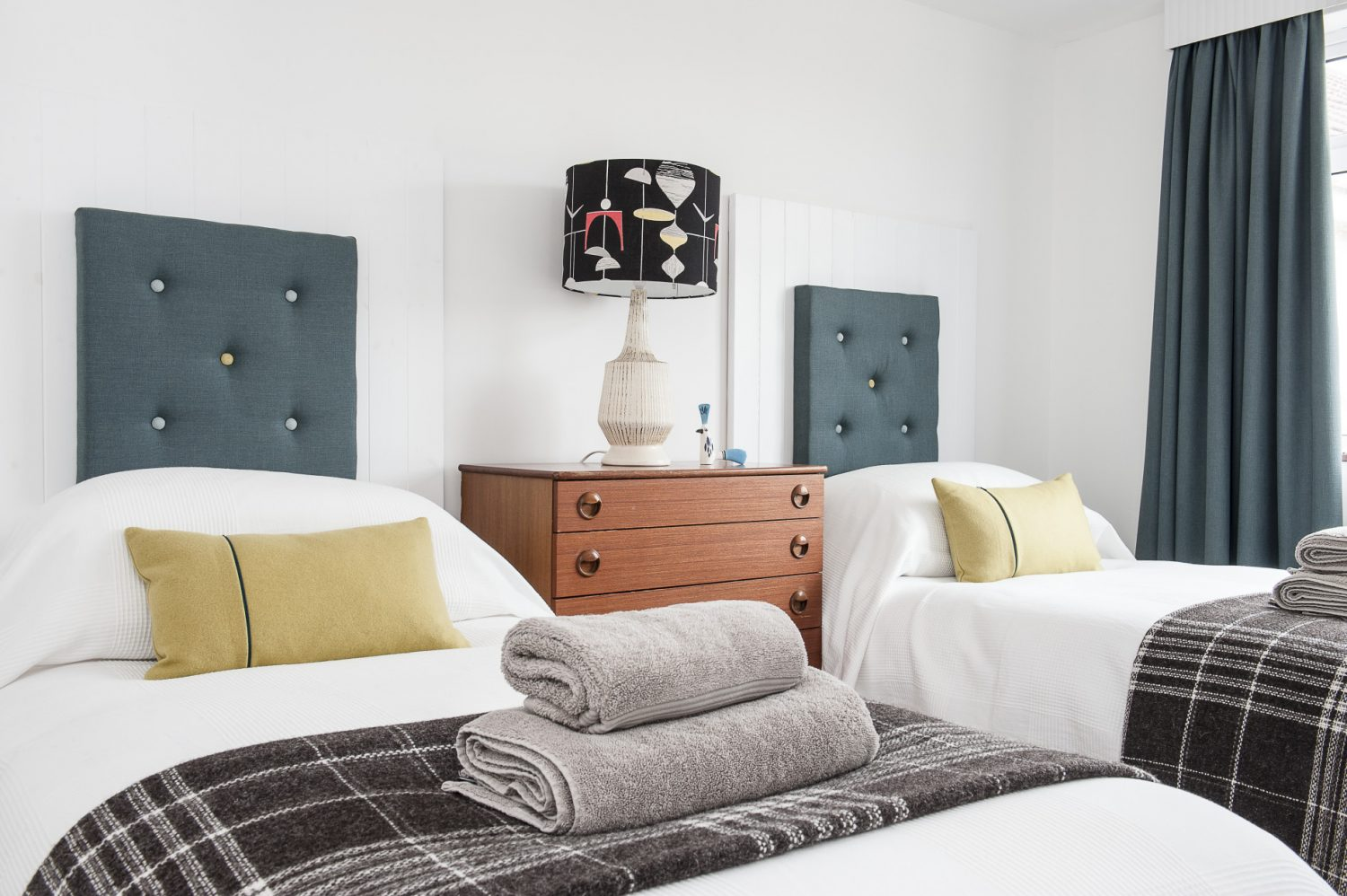 A third bedroom is nestled on the ground floor. James has once again employed his creative skills to make painted wooden headboards onto which he has mounted upholstered squares. A trio of framed album covers are mounted onto one wall