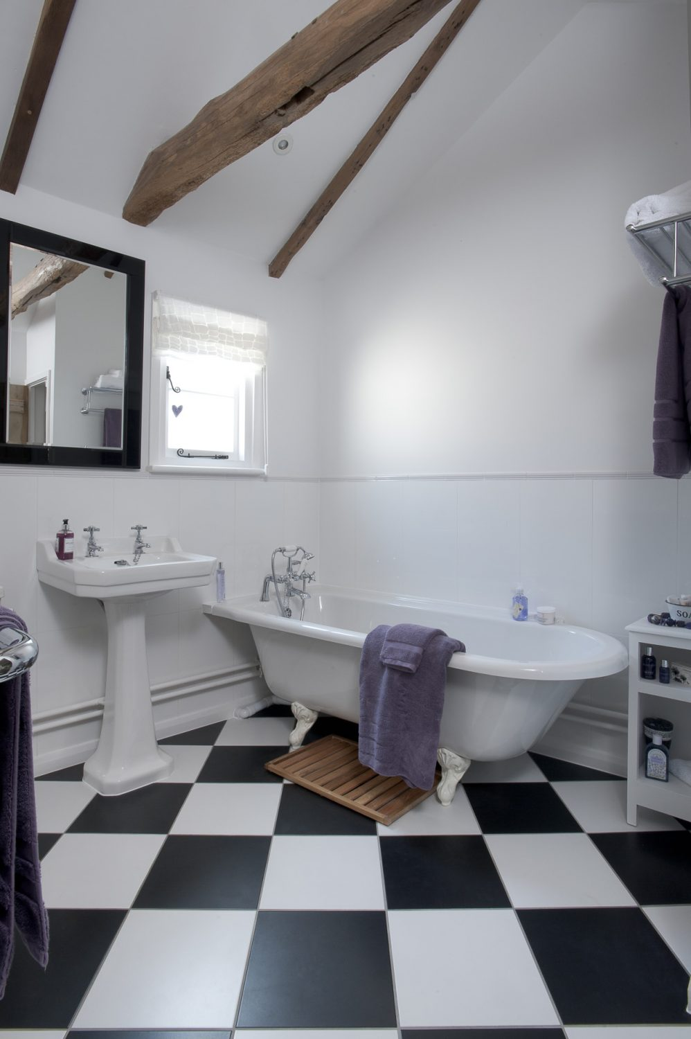 The bathroom next door features black and white diamond floor tiles, a roll top bath and a Savoy style pedestal basin underneath a piano black framed and bevelled mirror