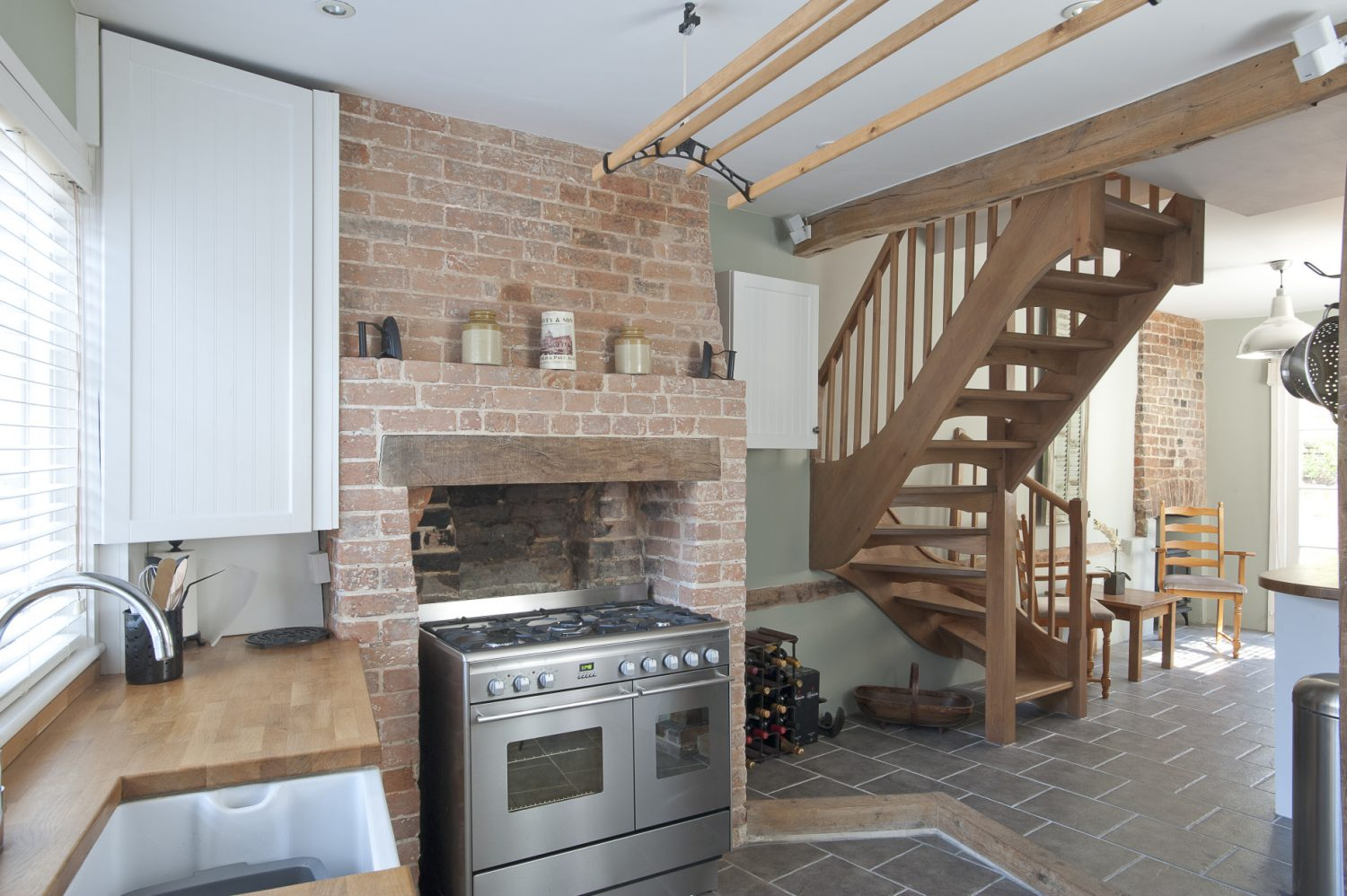 In the kitchen, a stainless steel range cooker has been placed in the wide fireplace