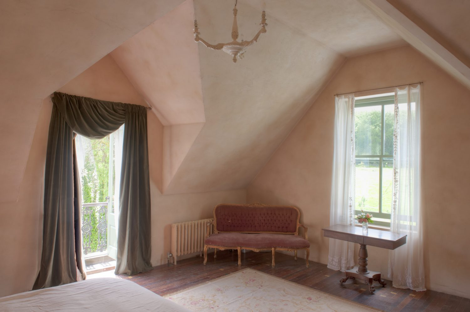 A huge bed in the principal bedroom looks out across the meadow and woods through the window at its foot