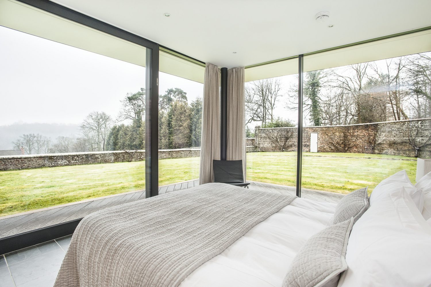 The end bedroom's two exterior glass walls look out over the lovely terraced garden