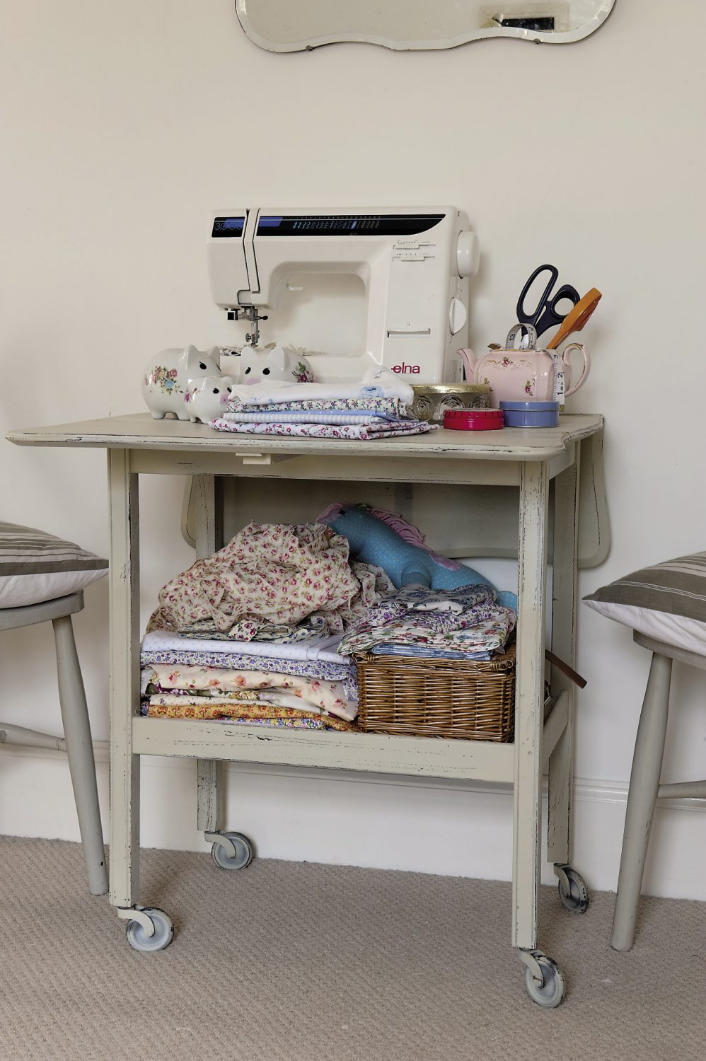 Piles of neatly-folded fabric beneath Anastasia's sewing machine await transformation into bunting