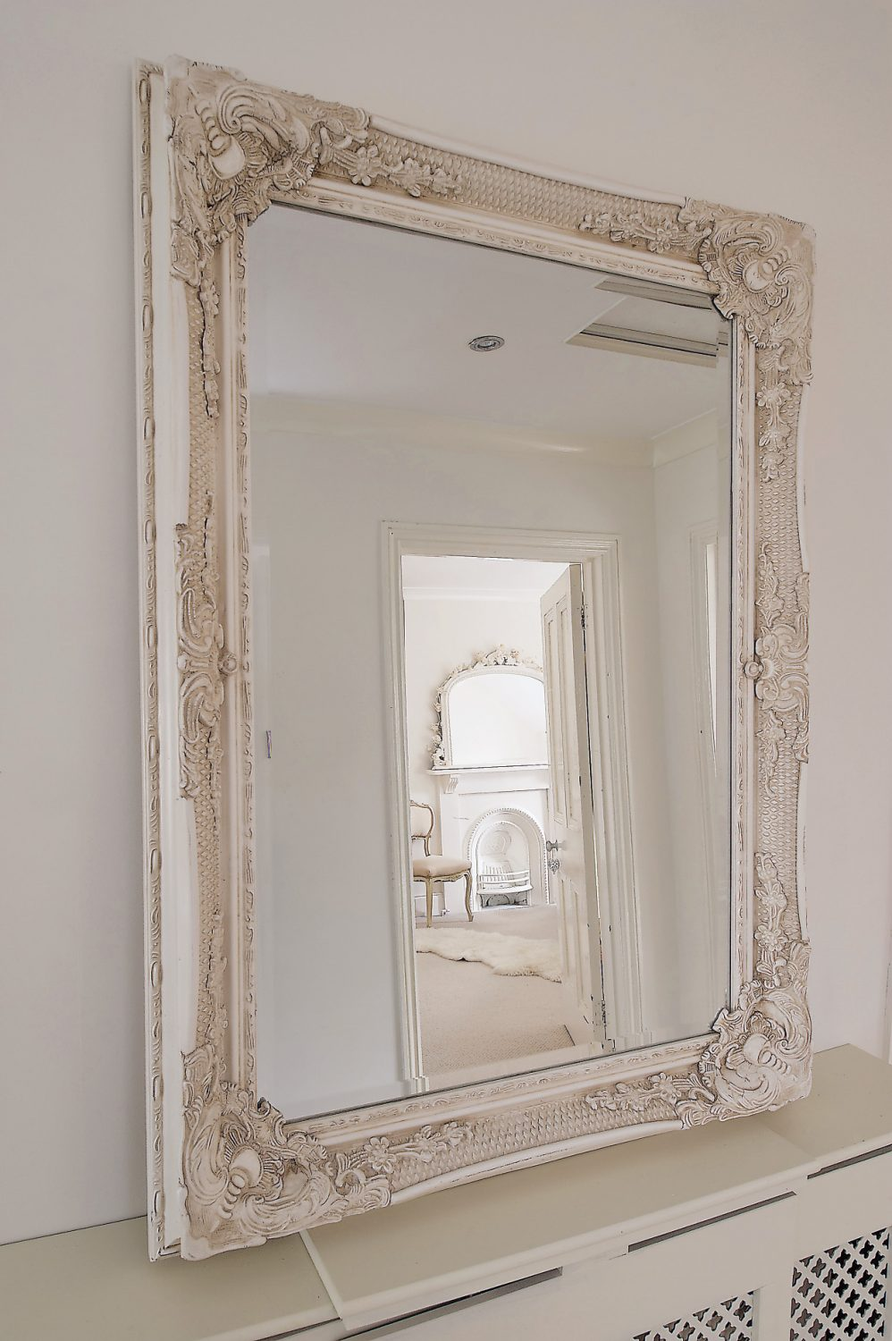 In front of the fireplace there is a dainty Rococo style bedroom chair upholstered in shell pink silk, antique lace camisoles hang from the door of one armoire and a garland of voile roses entwined around the frame of an overmantel mirror all add to the sense of luxurious indulgence
