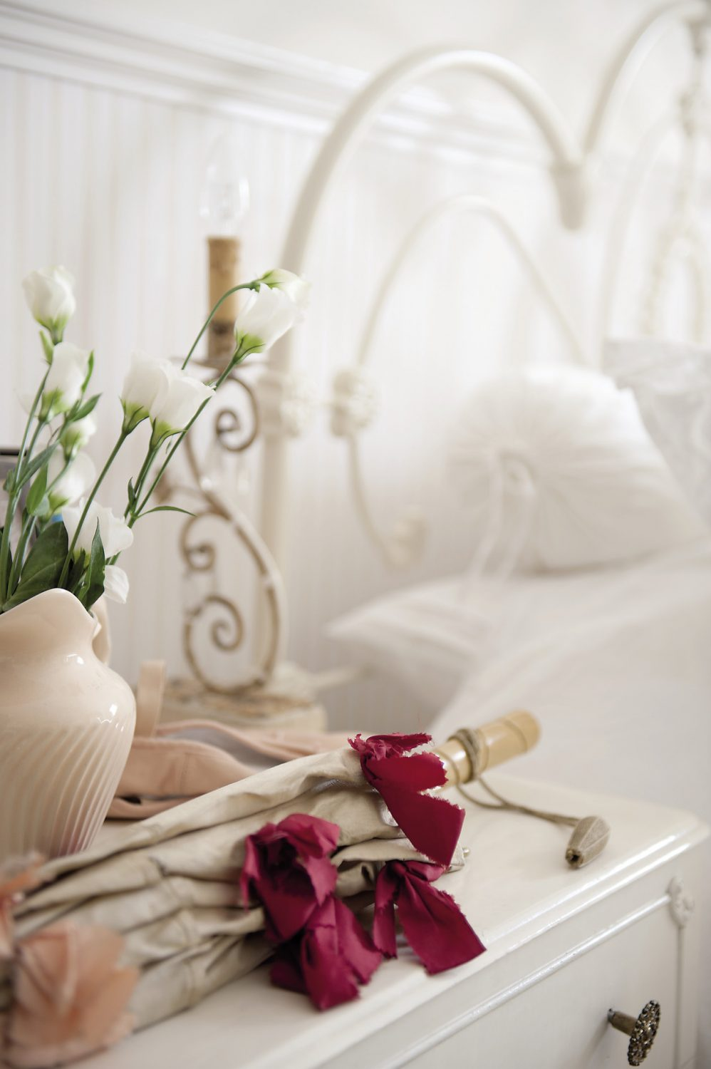 Anastasia's wrought iron bed is dressed with antique embroidered linen as well as a cable knit blanket from Ralph Lauren and a patched sheepskin throw. An antique parasol and ballet shoes rest on the bedside table