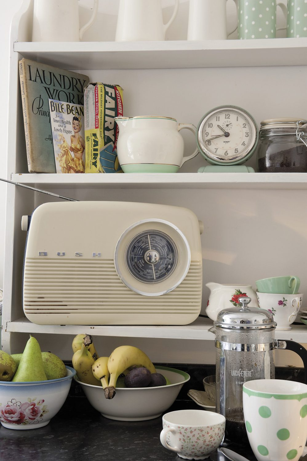 A retro style ivory Bakelite Bush radio stands on the shelves above the kitchen counter and there are more cream and green enamel storage tins as well as a large bar of 'Fairy' household soap in its original 1950s packaging
