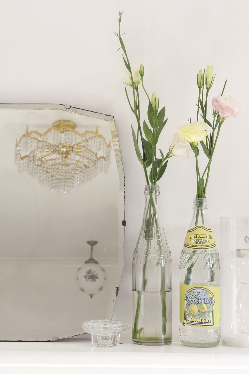 On either side of the mirror Anastasia has arranged small groups of vintage lemonade bottles filled with pale yellow and shell pink lisianthus
