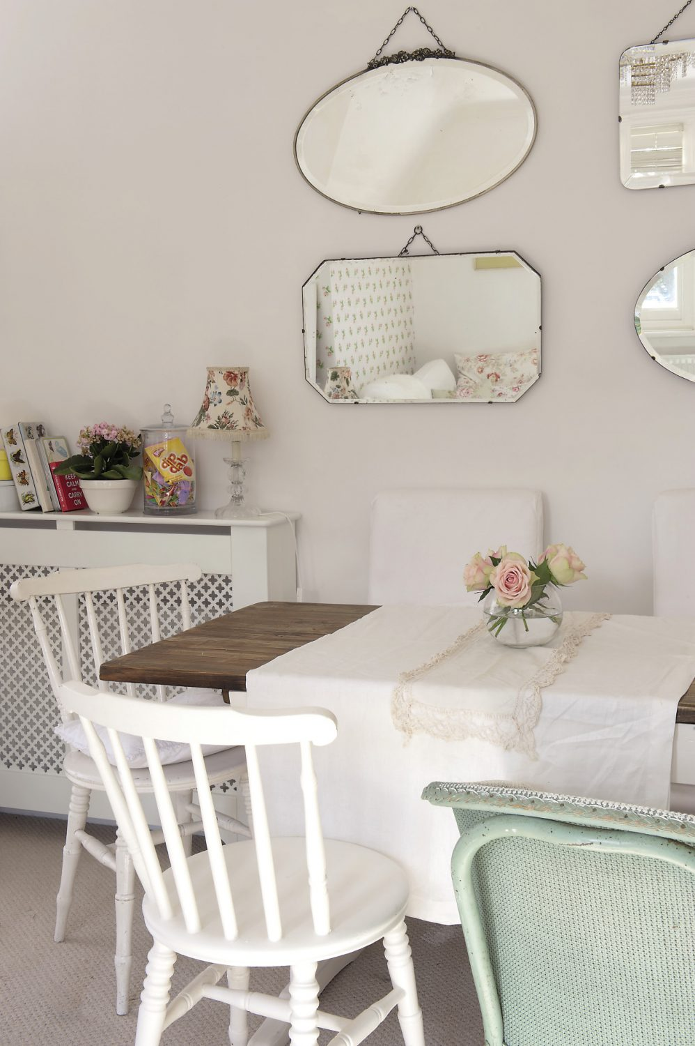 Mismatched chairs surround the rectangular French refectory table, and in the centre of the linen and lace runner there is a small glass vase of pale pink roses with pistachio green outer petals. On the wall above, Anastasia has grouped together four bevelled mirrors of varying shapes