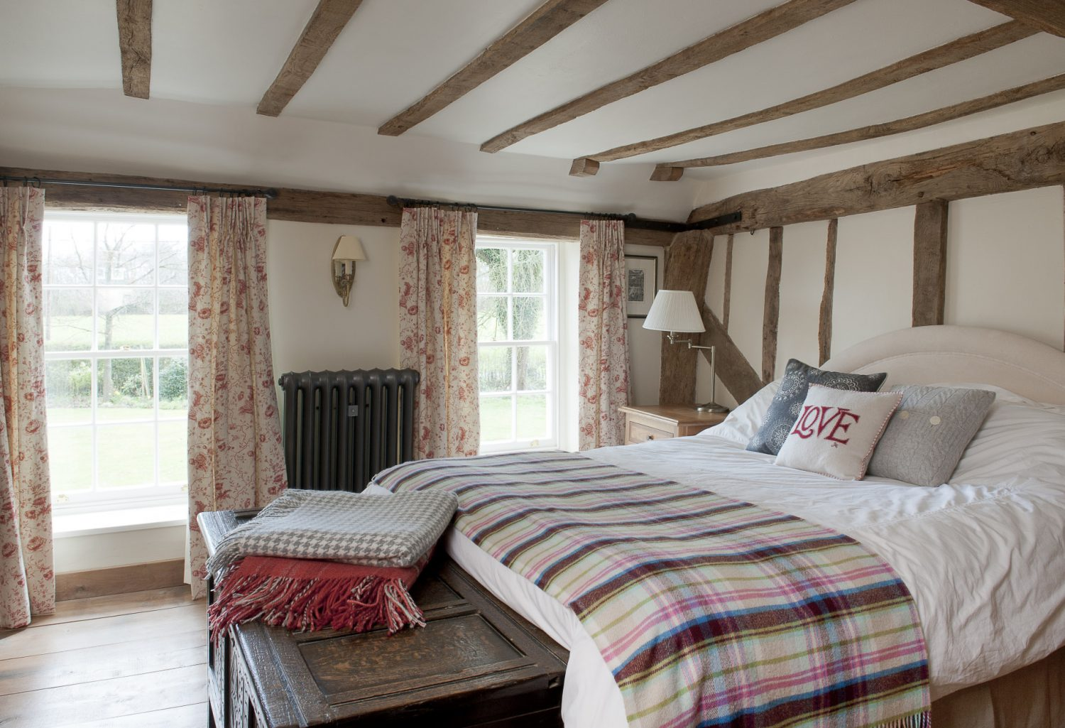 The guest bedroom is simply furnished with soft red and cream floral toile curtains and a bed dressed with white cotton and a cosy check blanket. A dark carved oak blanket which box stands at the end of the bed is another of Richard's student projects