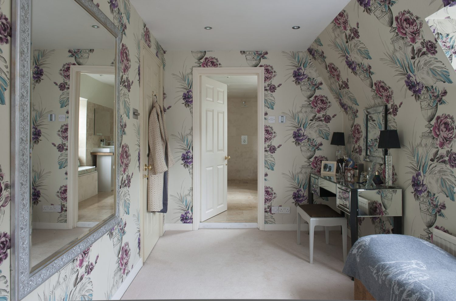 The master bedroom dressing area has been decorated in a gloriously exuberant Designer's Guild floral paper. A door to one side leads into a wet room, where a window seat is upholstered in a duck egg blue GP & J Baker print, above which sit Chinese vases