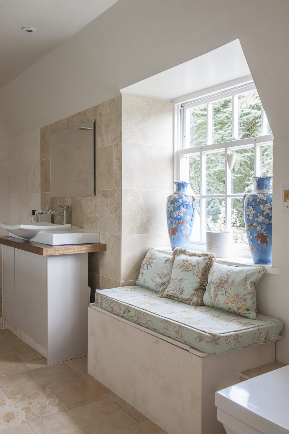 A door to one side leads into a wet room, where a window seat is upholstered in a duck egg blue GP & J Baker print, above which sit Chinese vases