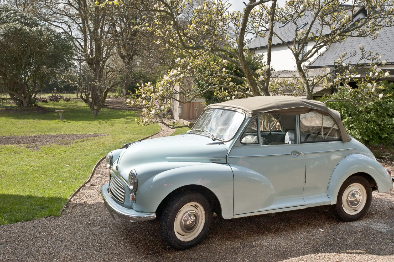 A convertible Morris Minor, inherited by Alice when a friend moved abroad, is parked proudly outside the house