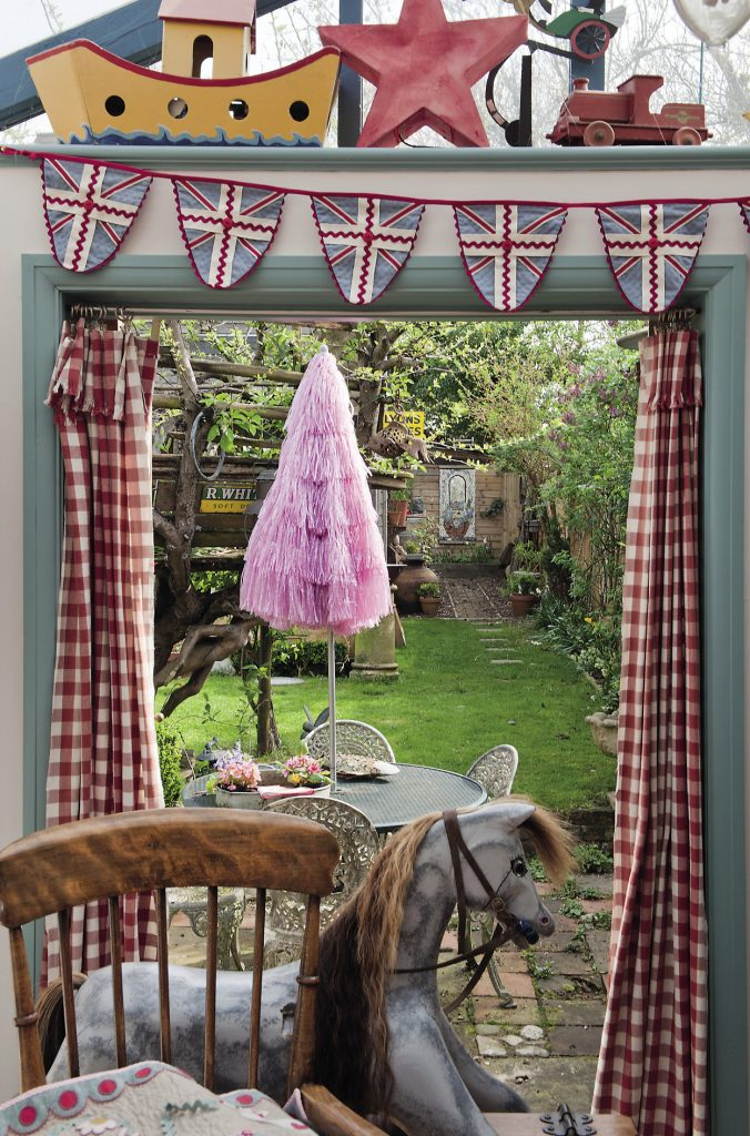 """Union Jack bunting hangs above the open French doors to the garden. Just in front of the French doors stands a handsome dapple-grey rocking horse. """"Phil made that for the children and put a time capsule in it, and he made the hobby horse, the wooden Noah's Ark and the train on the shelf above too,"""" says Mandy"""