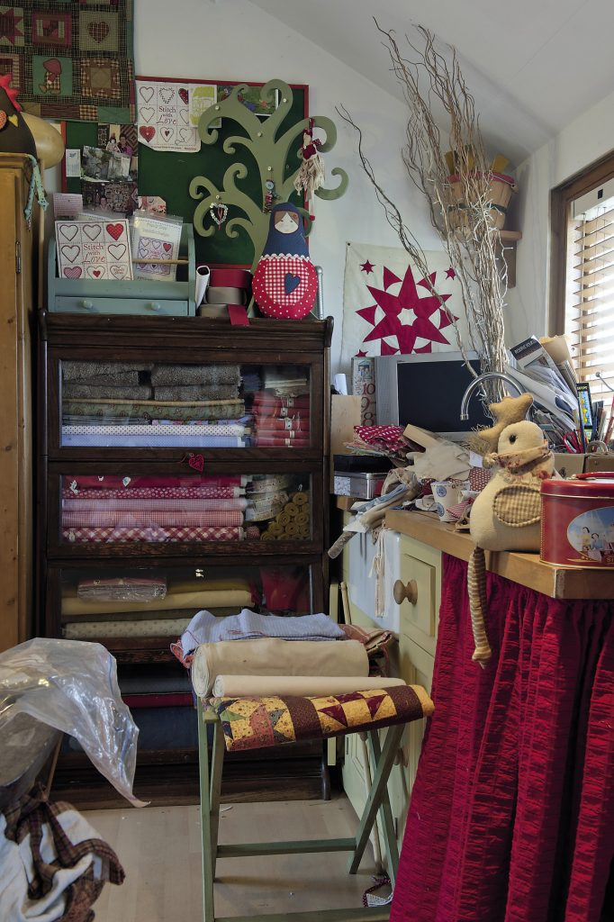 At the bottom of the garden we climb the stairs to Mandy's studio. Almost every patch of wall is covered in shelving that seems to be groaning under the weight of books, fabrics, patterns, cotton reels, completed and unfinished quilts, soft toys and baskets of ribbons and trimmings