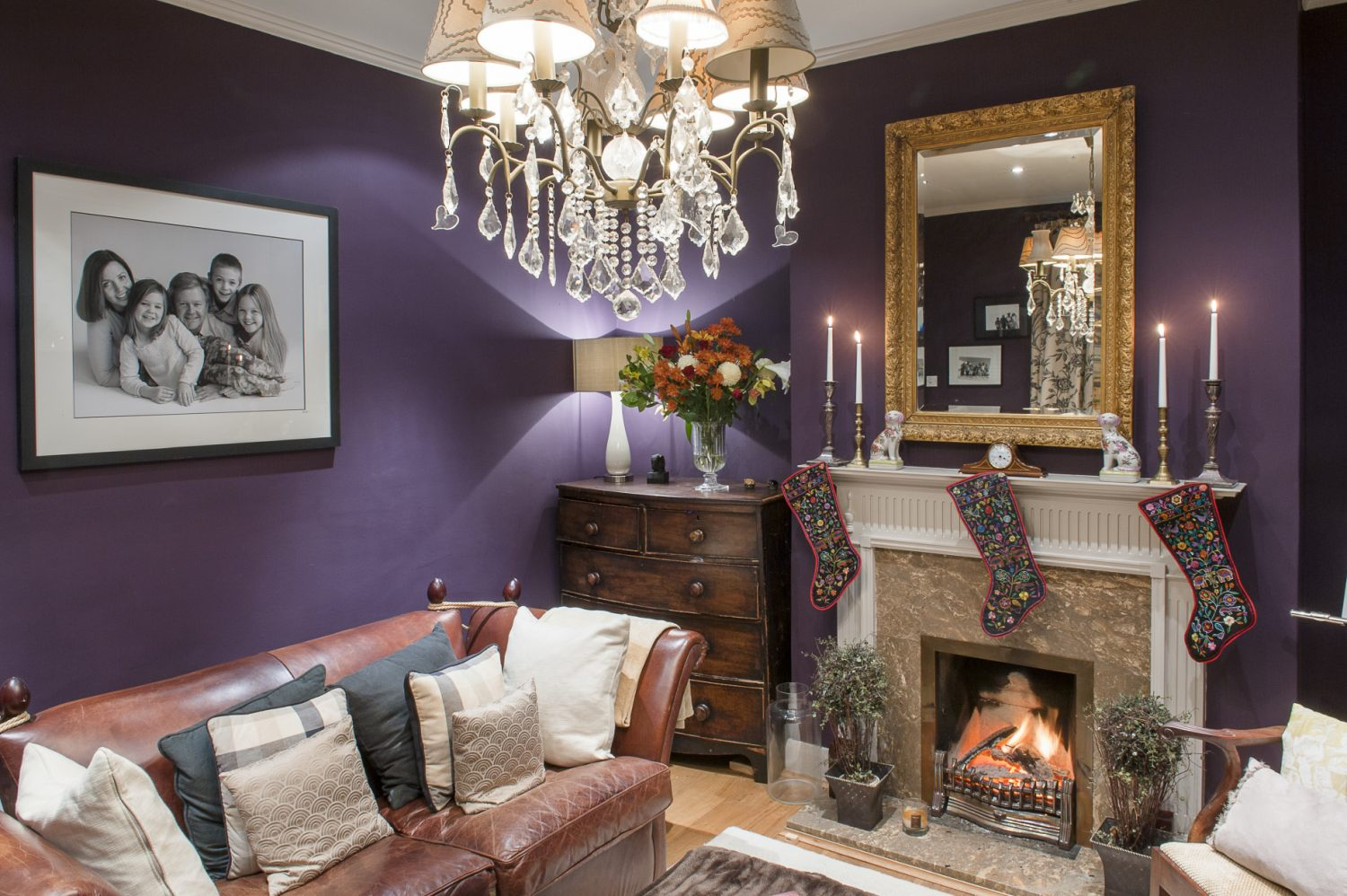 The snug is painted a rich, dark and opulent aubergine. Stockings hang neatly above the open fire, whilst a gilt-edged mirror above reflects the candlelight around the room. A chandelier from Mister Smith Interiors hangs from the centre of the ceiling