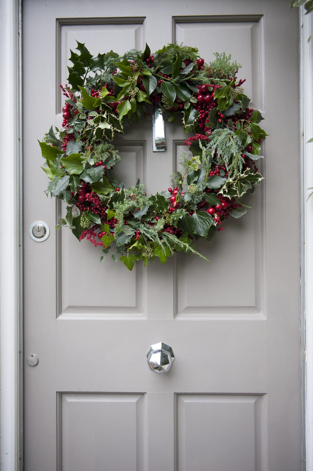 A freshly-made wreath studded with jewel-red berries greets visitors to the front door