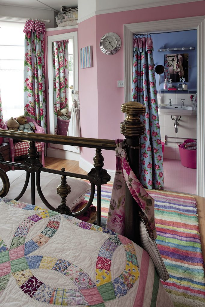 A pink-painted Lloyd loom chair stands in one corner of the room and a striped IKEA rug stretches out across the floor