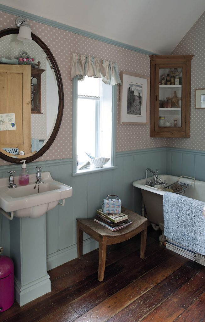 The family bathroom is decorated with tiny star patterned wallpaper and duck egg blue painted matchboard panels. Striped linen blinds hang at the windows and a reclaimed roll-top bath stands on dark stained floorboards