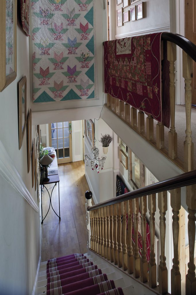 On the landing, there are more quilts hanging on the walls and over the banister