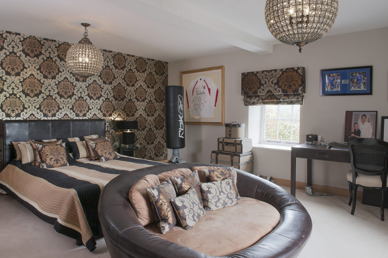 Claire's son Josh's room is papered in a striking cream, gold and chocolate damask-style wallpaper which complements the bold striped bedcover, leather sofa and campaign-style leather desk