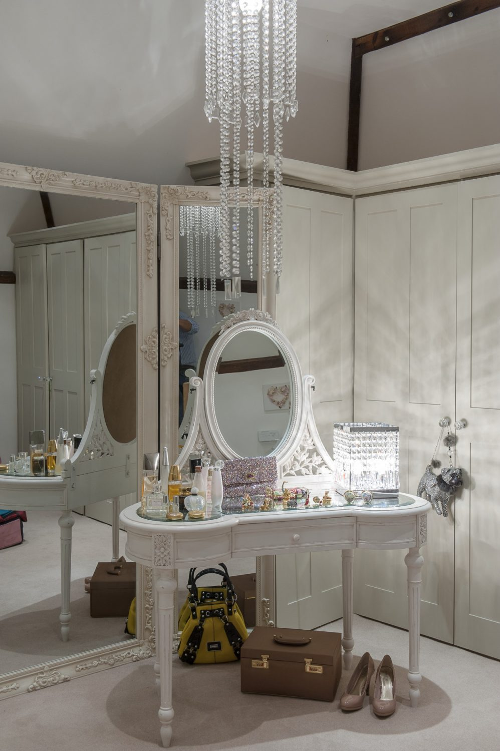 In the dressing room, fitted wardrobes line two walls. A chandelier hanging from the ceiling adds to the unabashed sense of glamour
