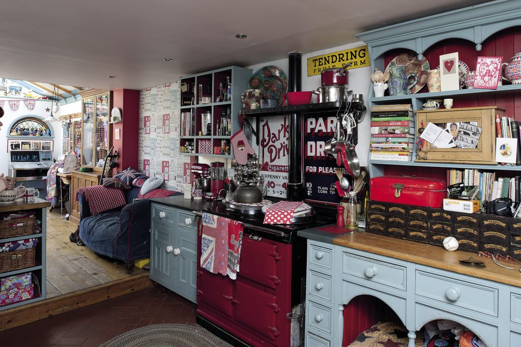 The kitchen is a riot of red, white and blue, with Union Jack cushions scattered about on the sofa and armchair. The table is covered in a red and white spotted oilcloth and stands in the glass ceilinged breakfast/dining room that the couple built onto the back of the house
