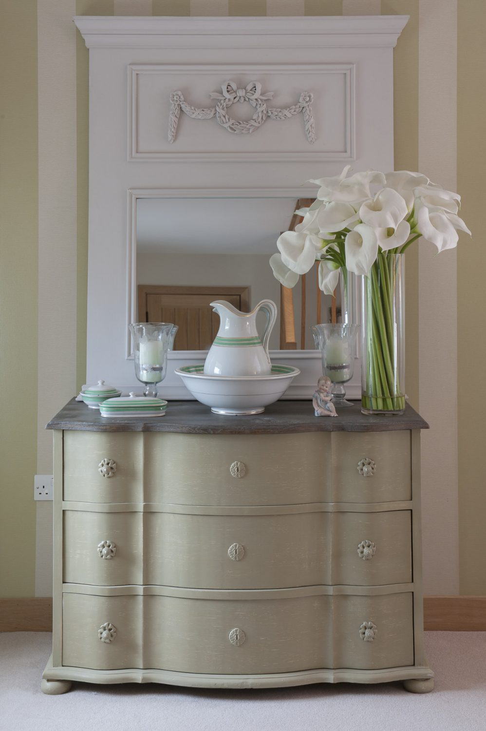 A bombe style painted chest is home to antique washstand china with emerald green and gold stripes