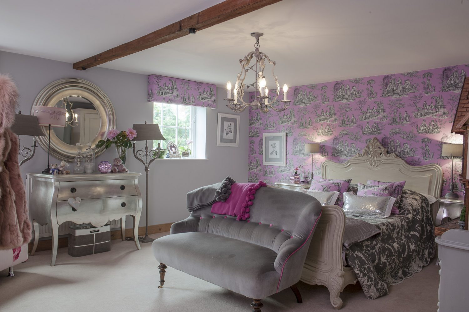 The guest room has been papered with Manuel Canovas toile in a mauve and elephant grey. An ornately carved bed is dressed with a charcoal grey toile bedcover, silver silk quilt and shimmering sequinned cushions