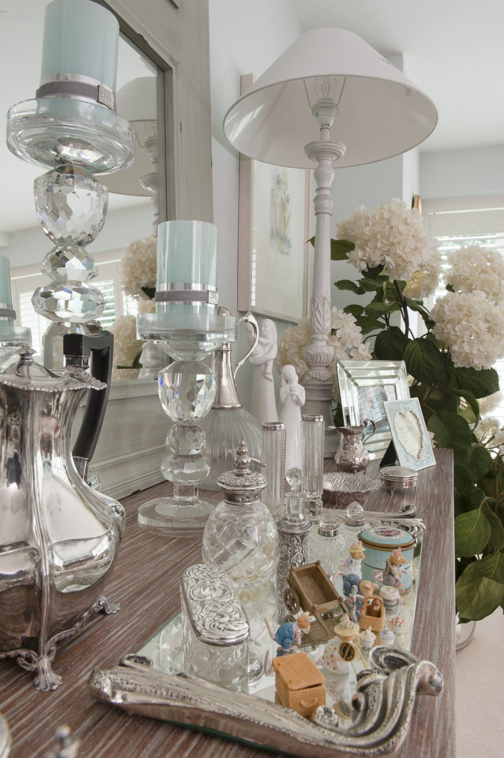 At the other end, an oak-topped painted dresser displays a collection of silver and Venetian glass-framed family photographs, glass candlesticks and silver-topped glass decanters