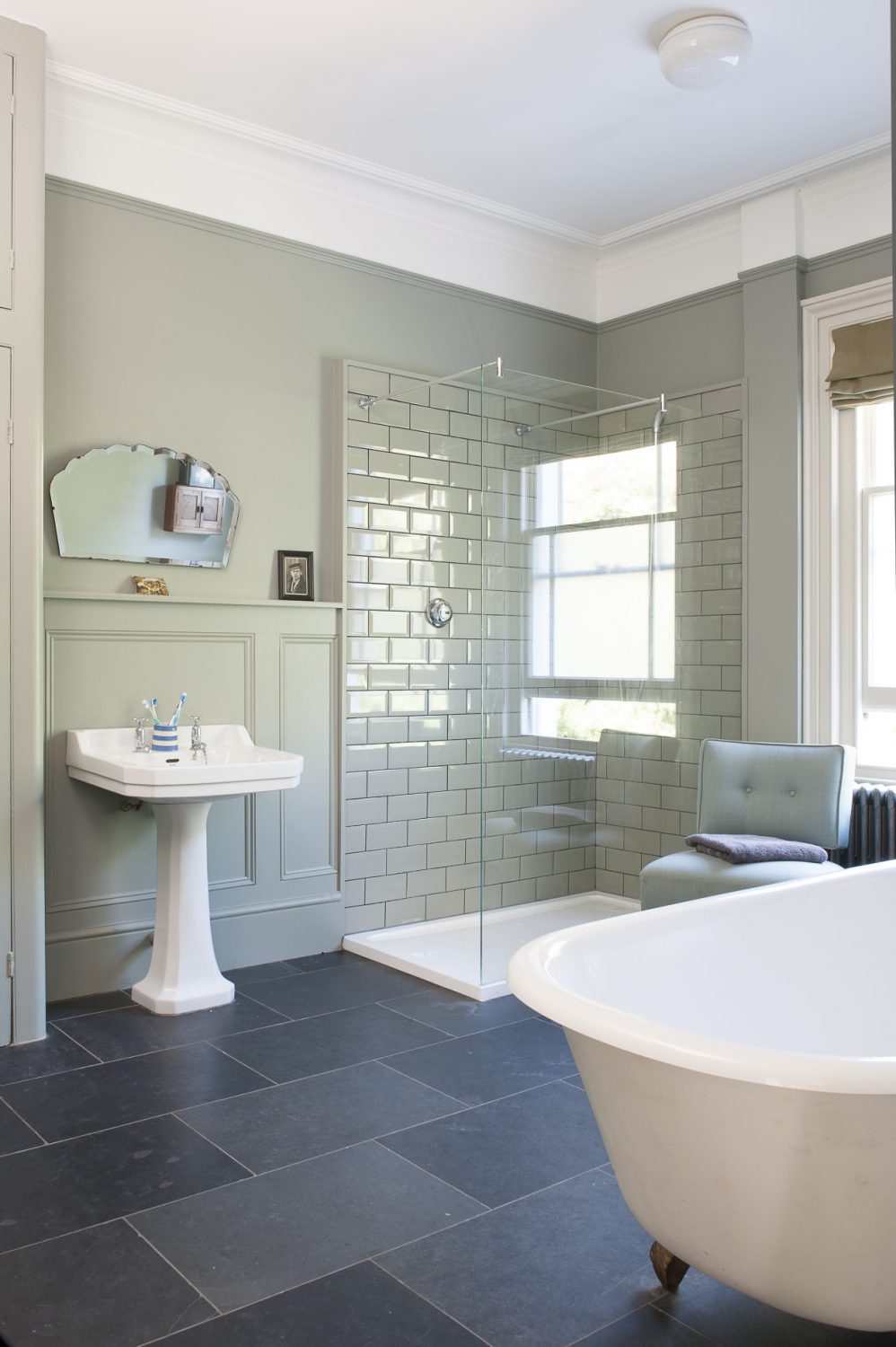 Across the landing, the bathroom has been painted F&B's Pigeon that neatly emphasises the handsome wooden wall panelling