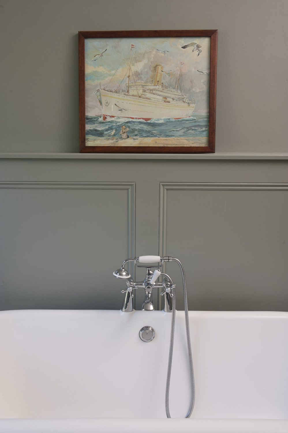 A huge rolltop bath stands against the opposite wall, where Sarah has hung a picture of an ocean liner by Claire Fletcher that she bought for her eldest daughter from Made in Hastings