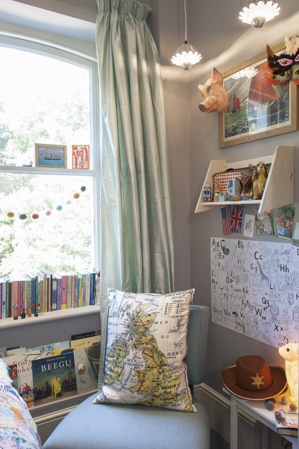 The couple's children have obviously inherited their parents' love of books and graphic art, too, because they all give books pride of place. In their youngest daughter's room there is a little sea green bedroom chair with a silk cushion featuring a map of the British Isles, and a table with a milky white rabbit nightlight to banish the dark.