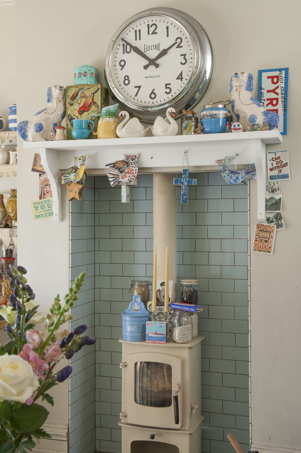 A duck egg blue tiled alcove houses a woodburning stove