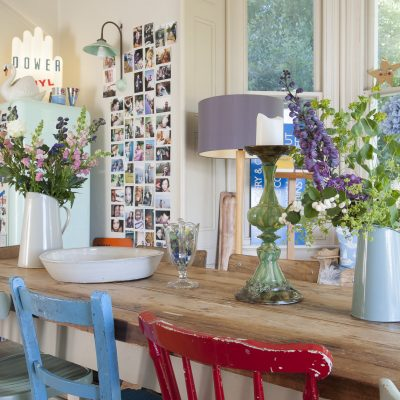 In the kitchen, a collection of vintage school and bentwood chairs are gathered around a long, narrow, scrubbed wooden refectory table