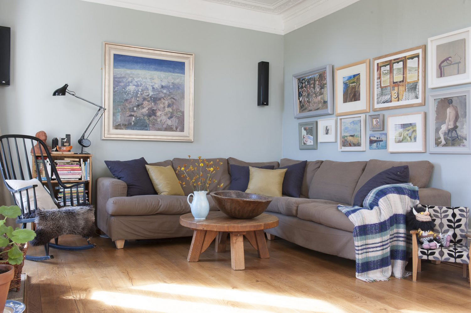 The drawing room, painted in F&B's Light Blue, features a dark mushroom coloured, tweed covered corner sofa, dressed with pale chartreuse green and dark navy cushions and a striped throw