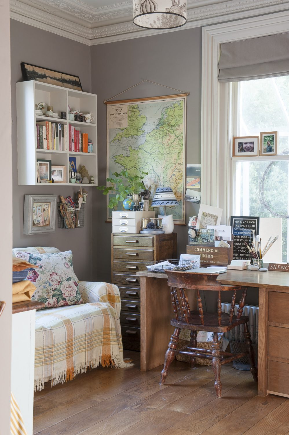 Next to a long sofa, covered with a vintage wool blanket, hangs a waxed schoolroom map of France