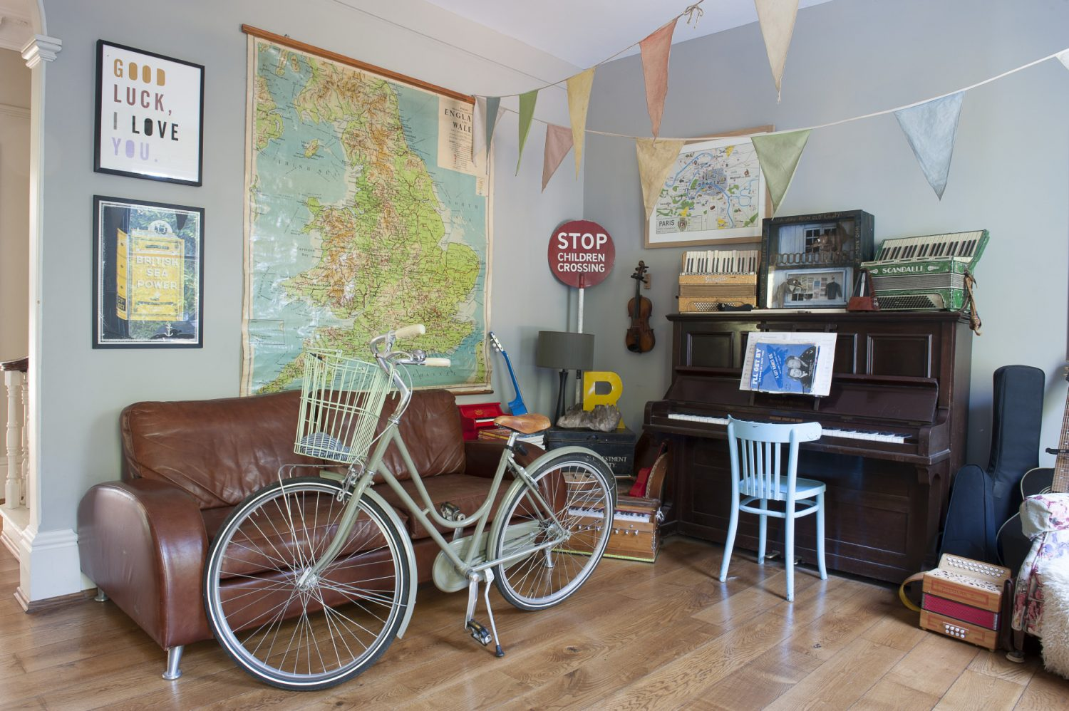 The entrance hall, swathed in bunting, is home to an upright piano as well as several accordions. On top of the piano sits a Len Shelley bird artwork that Sarah bought her husband for his 40th birthday