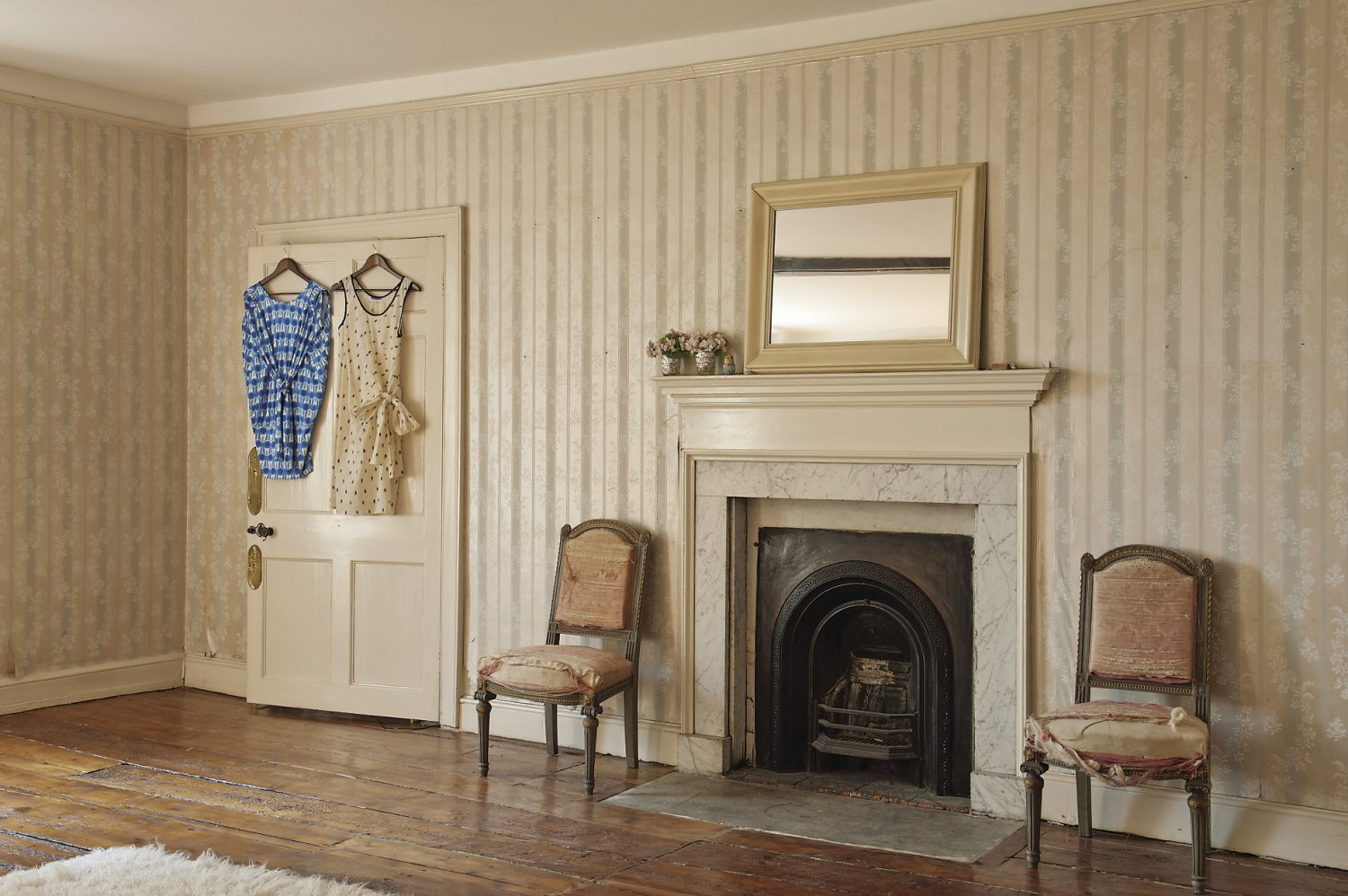 """A spacious guest room has a striped and swagged wallpaper. A pair of French chairs also stand either side of the iron fireplace: """"My friend said they weren't so much shabby chic as s***** shack,"""" says Gabby. """"We haven't changed any of the wallpapers on this floor and I think they've been here since the 1940s or 50s."""""""