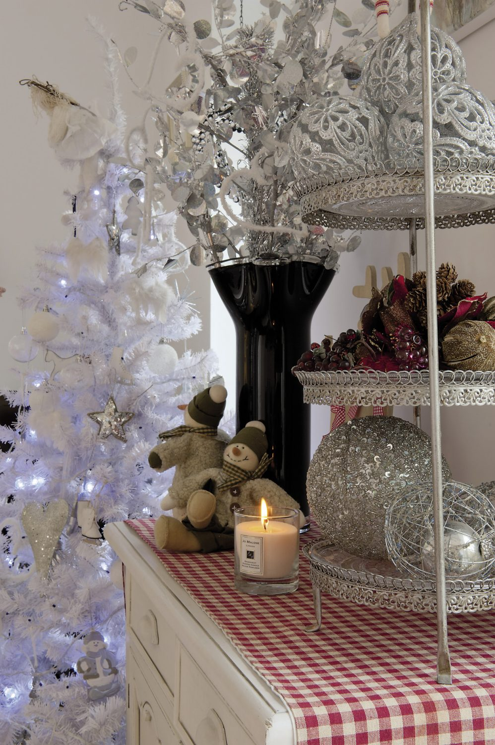 A striking silvery white Christmas tree is illuminated by frosty blue fairy lights and hung with crystal snowflakes, silver ice skates and milky white snowmen
