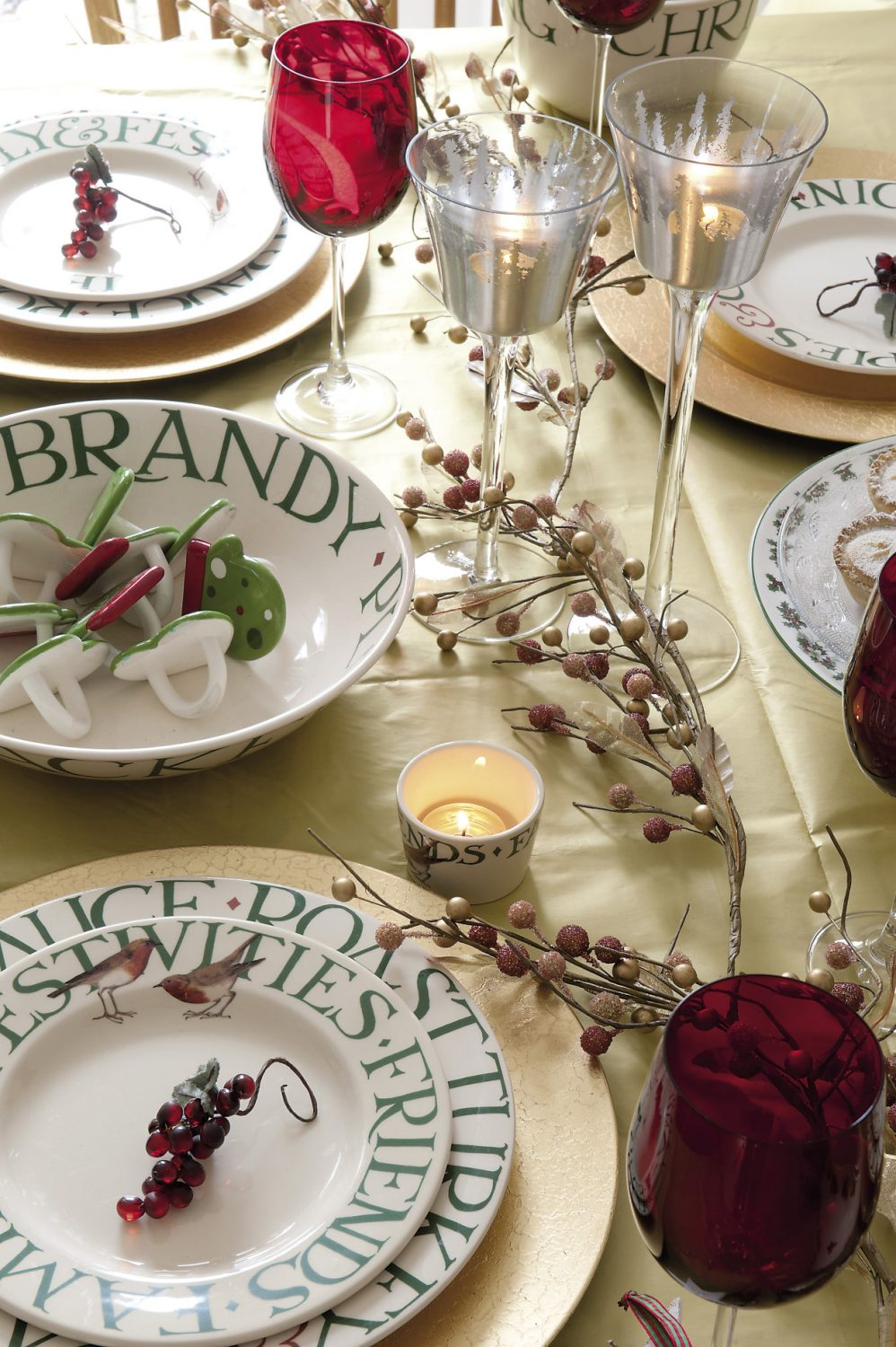 The dining table in the living room is laid with Christmas crockery as well as cranberry glasses and a gold tablecover strewn with faux berries and silver stars