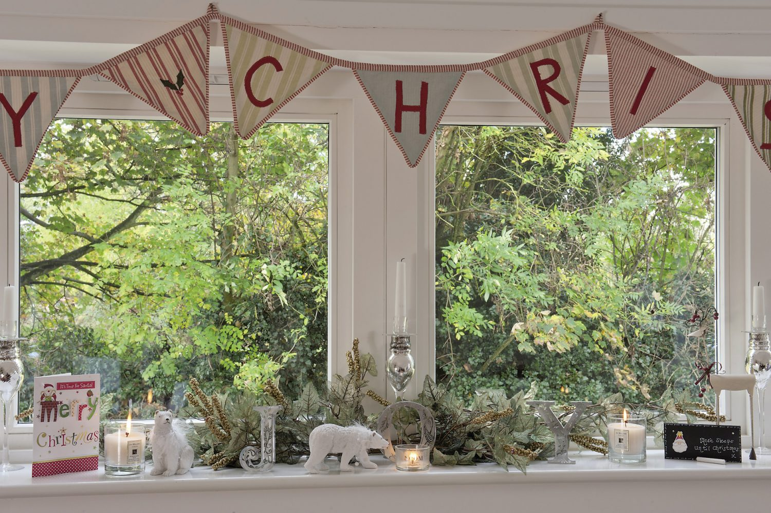 The sitting room window is draped with Christmas bunting, while on the counter in the kitchen, the festive baking books and bowls are at the ready