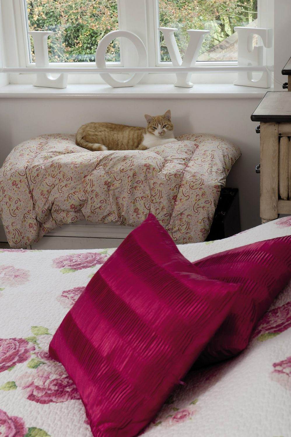 The bed in the master bedroom is covered with an Italian handmade quilt festooned with vivid pink and red blousy roses on one side and delicate rosebuds on the reverse