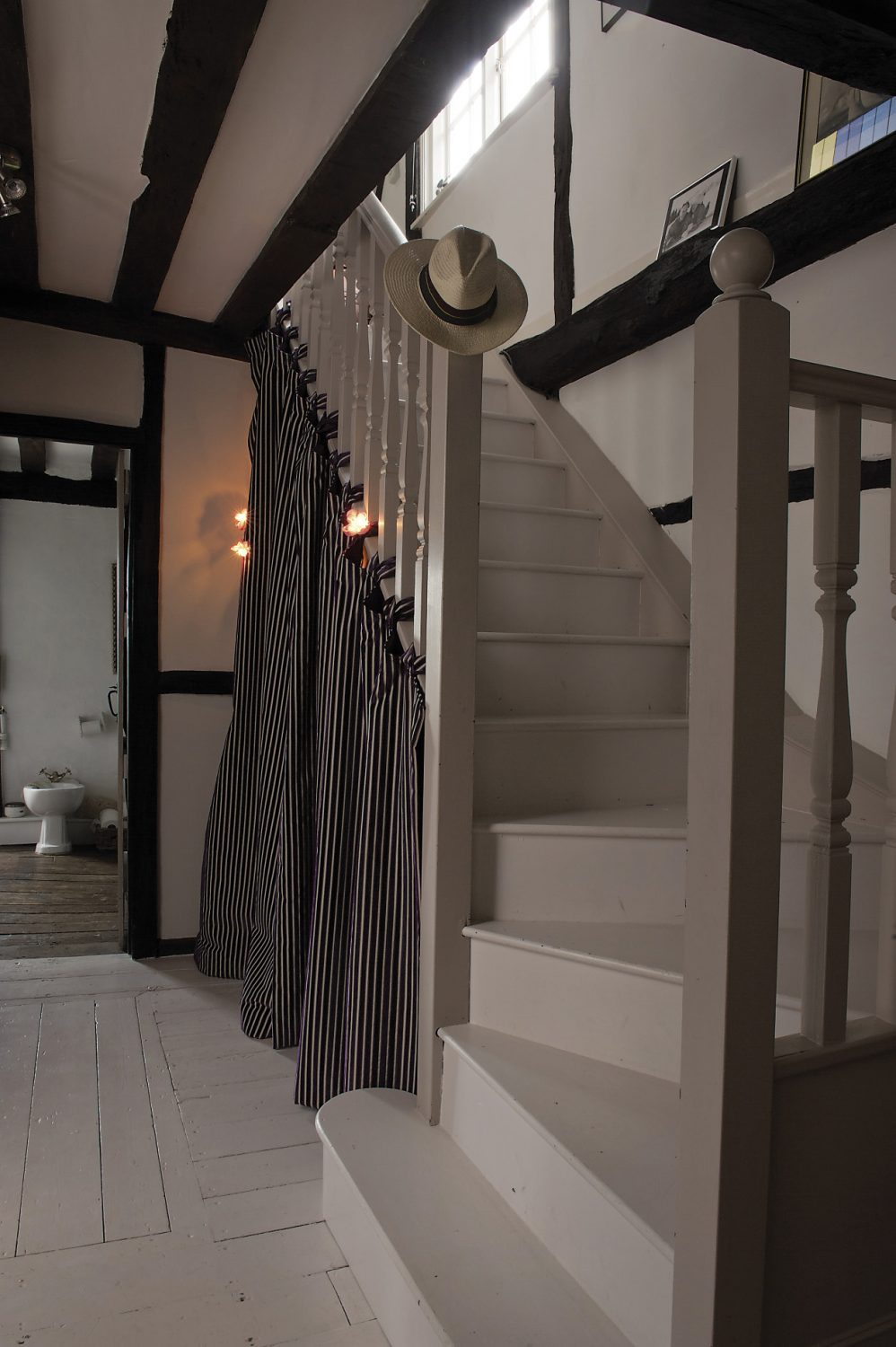 Stairs lead off from the landing up to the second floor. Emma has cleverly screened off the space beneath the stairs to house shoes and clothes, illuminated by fairy lights