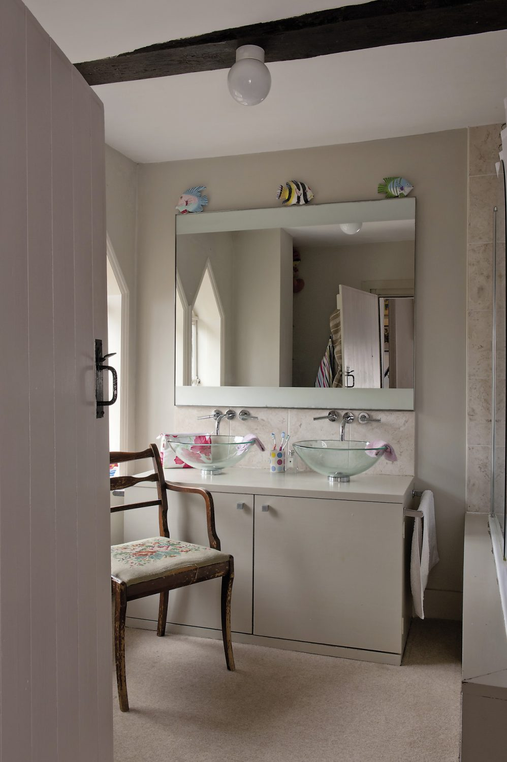 A newly refurbished bathroom features strikingly contemporary glass twin basins