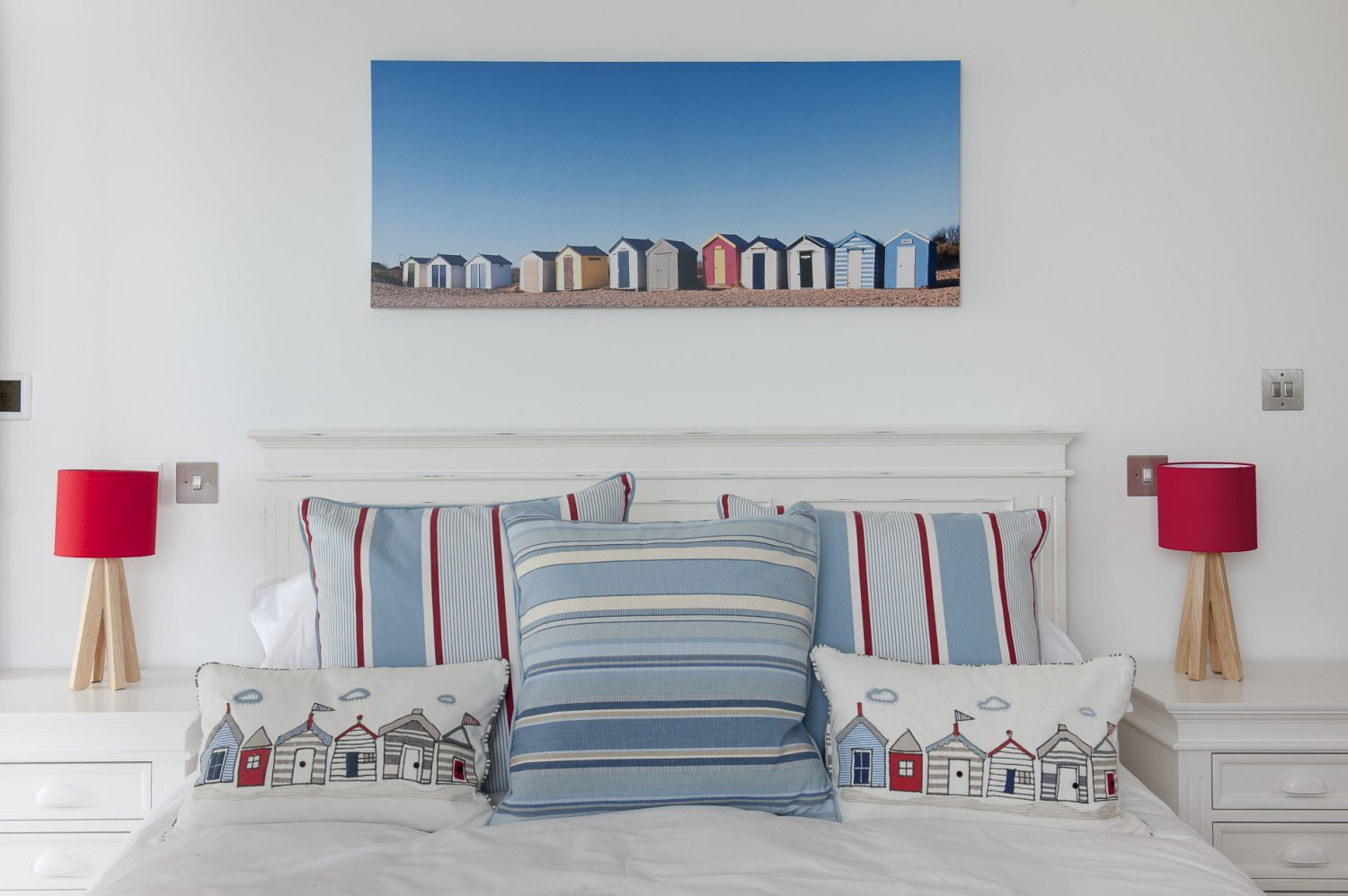 A guest bedroom is decorated in Sea Gem's signature nautical colours, with bold, sky blue and scarlet stripes set against pure white bedlinen. On the wall above the bed is a vividly coloured wide angle photograph of painted beach huts by Gill Copeland