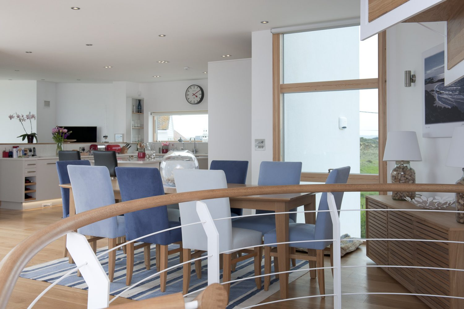 n the open plan dining area stands a long oak dining table surrounded by chairs covered in varying shades of blue family-friendly fabric