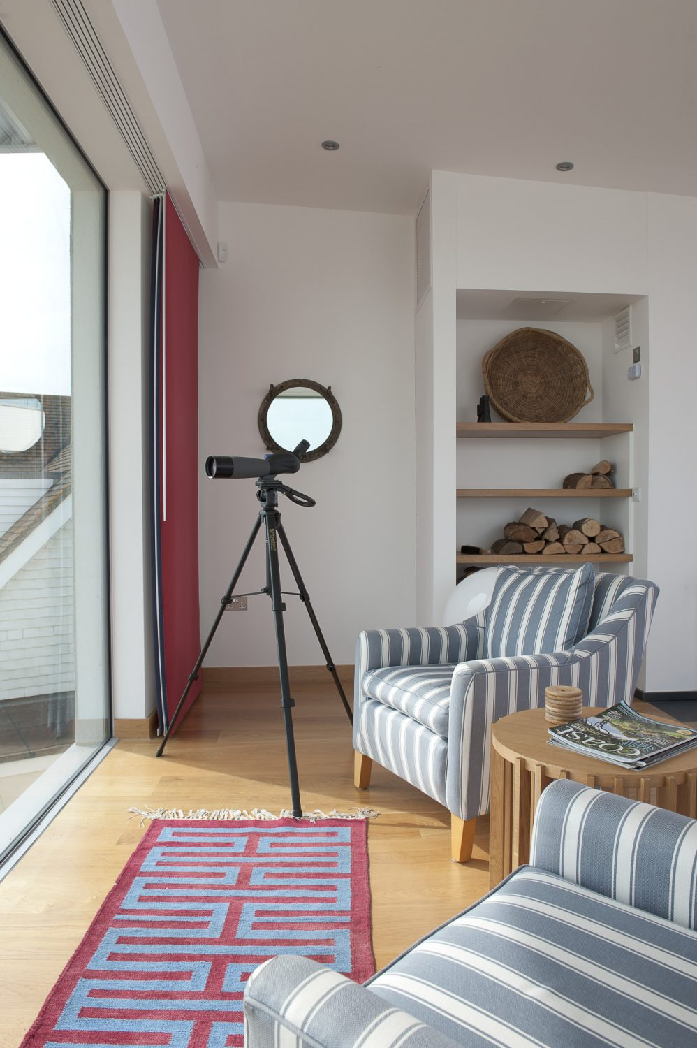 Two striped armchairs have been perfectly placed next to the windows with a telescope within reach